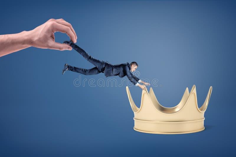 Een kleine zakenman probeert om greep van een grote gouden kroon te krijgen terwijl wordt gesleept weg door een reusachtige hand stock fotografie