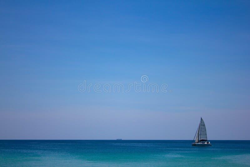 Een kleine zeilboot op de overzeese oppervlakte van het water op de horizon van zuivere blauwe hemel Mooi Zeegezicht Sereniteit royalty-vrije stock afbeeldingen