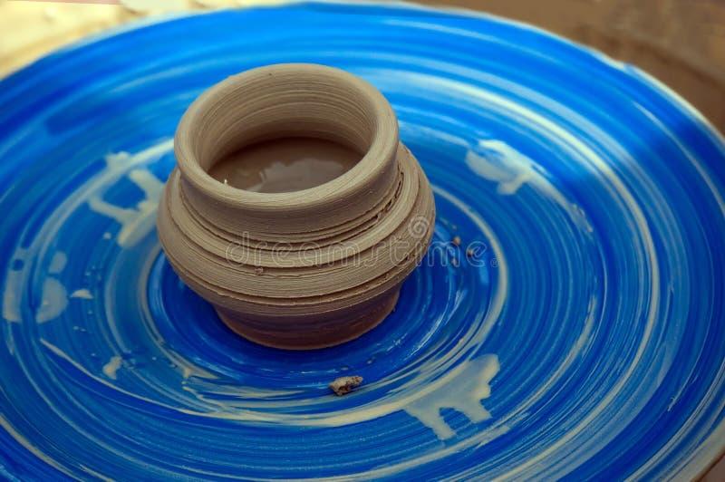 een kleiwaterkruik op een wiel van de Pottenbakker stock afbeeldingen