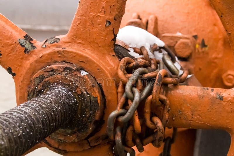 Een klepdeel van de olie en gas oude gekleurde oranje ketting van het systeemmetaal met grote verbindingenbescherming tegen inbra royalty-vrije stock foto's