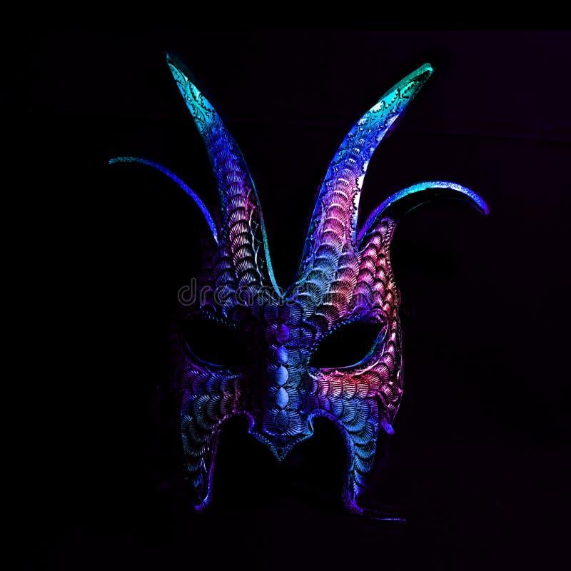 Een kleurrijk, eng Halloween-masker in blauw en purples tegen een zwarte achtergrond stock afbeeldingen