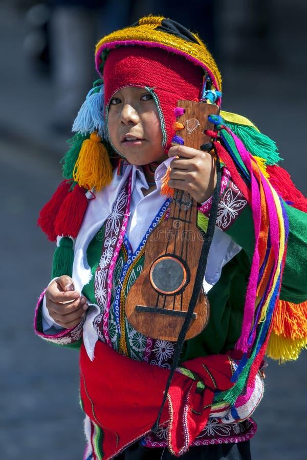 Een kleurrijk geklede jongen presteert onderaan een Cusco-straat tijdens de Meidagparade in Peru royalty-vrije stock foto's