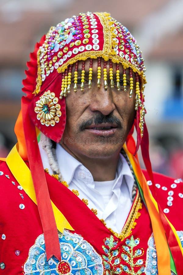 Een kleurrijk geklede mens stelt voor een phototgraph in een Cusco-straat tijdens de Meidagparade in Peru royalty-vrije stock afbeelding