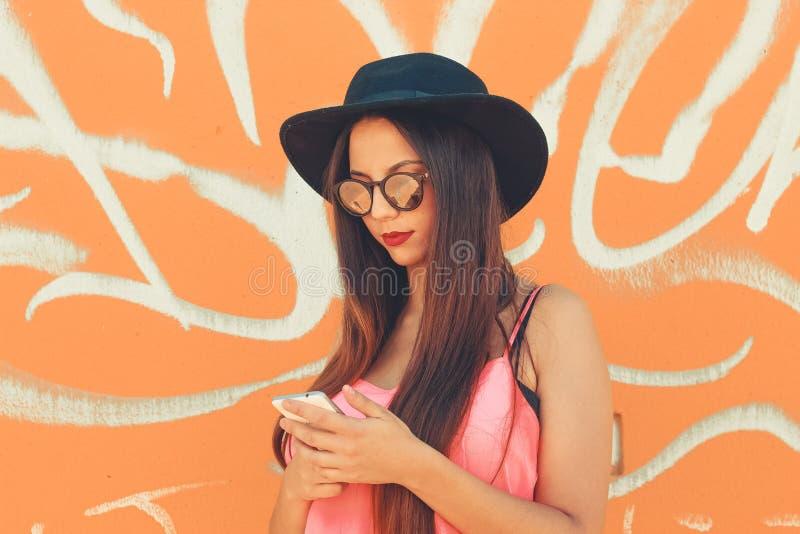 Een kleurrijk millennial meisjesoverseinen van haar mobiele telefoon royalty-vrije stock afbeelding