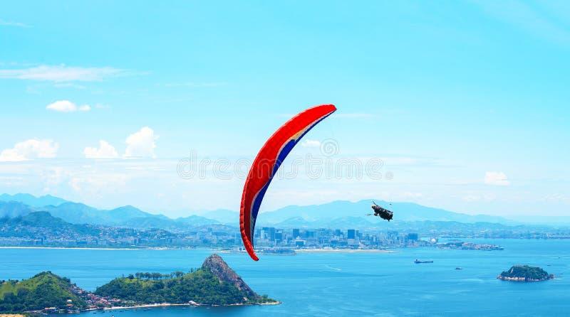 Een kleurrijk valscherm met skydiver op een zonnige blauwe hemelachtergrond Actieve levensstijl Extreme sport Het concept de zome royalty-vrije stock foto