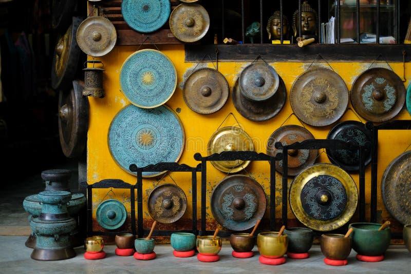 Een kleurrijke inzameling van siergongen, de de correcte kommen en standbeelden die van Boedha op een gele muur in een winkel han stock foto