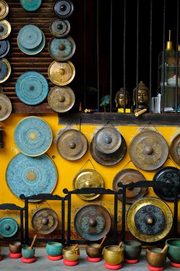 Een kleurrijke inzameling van siergongen, de de correcte kommen en standbeelden die van Boedha op een gele muur in een winkel han royalty-vrije stock fotografie