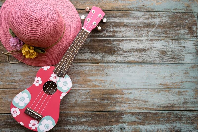 Een kleurrijke ukelele en een roze hoed bepalen op de uitstekende houten achtergrond stock afbeeldingen