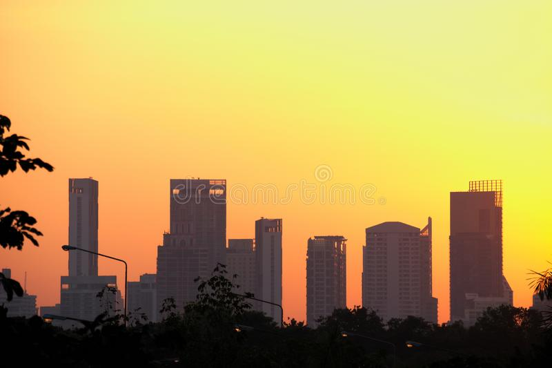 Een kleurrijke zonsopgang van oranje en gele tinten, over het donkere silhouet van Bangkok, Thailand royalty-vrije stock afbeelding