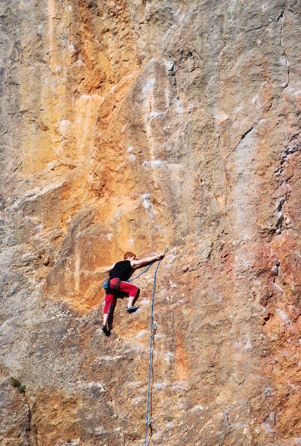 Een klimmer die de top bereiken stock afbeelding