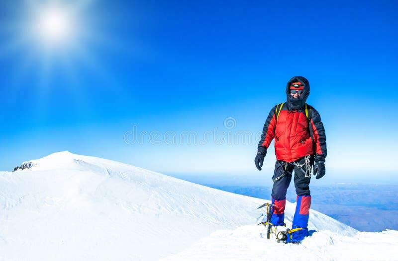 Een klimmer die de top van de berg bereiken stock foto's