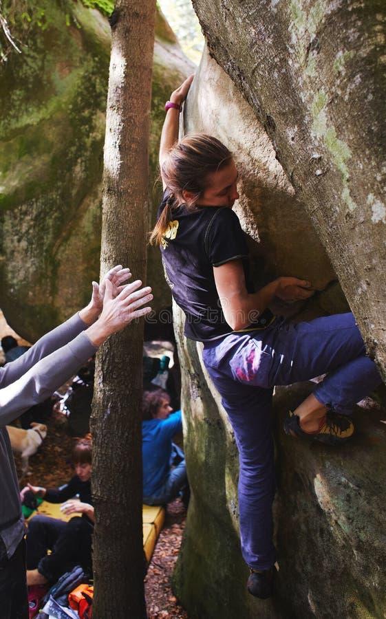Een klimmer die van de vrouwenrots een rots en haar partners het verzekeren beklimmen royalty-vrije stock fotografie