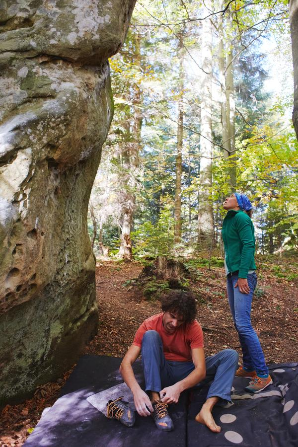 Een klimmer van de mensenrots treft voorbereidingen om een rots en zijn partner te beklimmen die op een rots letten stock afbeeldingen