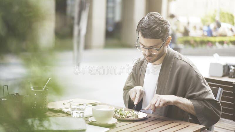 Een knappe gebaarde mens eet in openlucht alleen salade bij koffie royalty-vrije stock fotografie