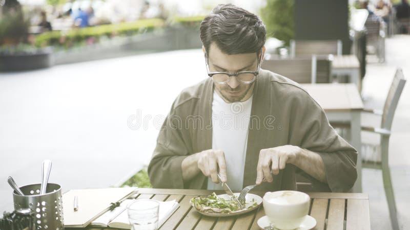 Een knappe gebaarde mens eet in openlucht alleen salade bij koffie stock afbeeldingen