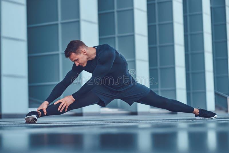 Een knappe geschiktheidsmens in een sportkleding, die het uitrekken doen zich terwijl het voorbereidingen treffen voor ernstige o stock afbeeldingen