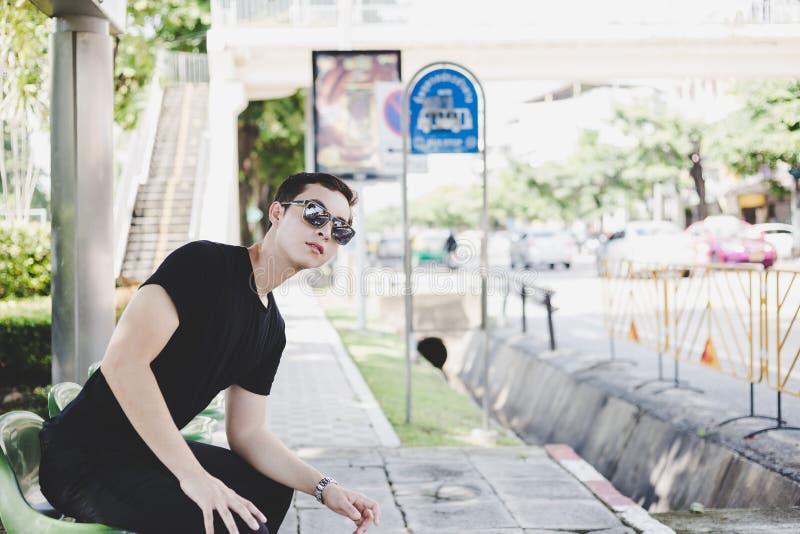 Een knappe jonge mens bekijkt een bus openbare bushalte en han stock foto