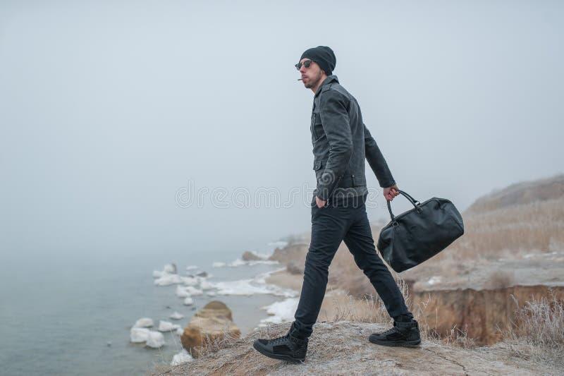 Een knappe jonge mens die in aard op rotsen lopen royalty-vrije stock afbeelding