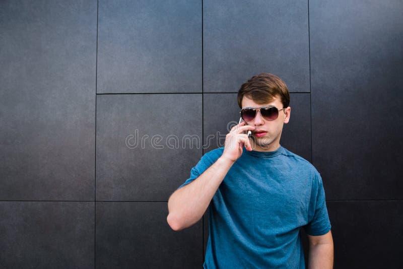 Een knappe jonge mens in glazen en een T-shirt spreekt telefonisch op de achtergrond van een grijze muur royalty-vrije stock foto
