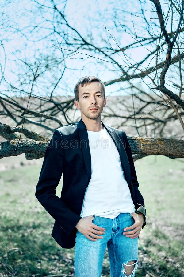 Een knappe jonge mens in een vest, zwarte broeken en een wit overhemd is st royalty-vrije stock afbeelding