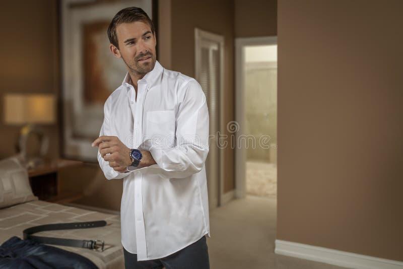 Een knappe jonge mens wordt gekleed in de slaapkamer stock fotografie