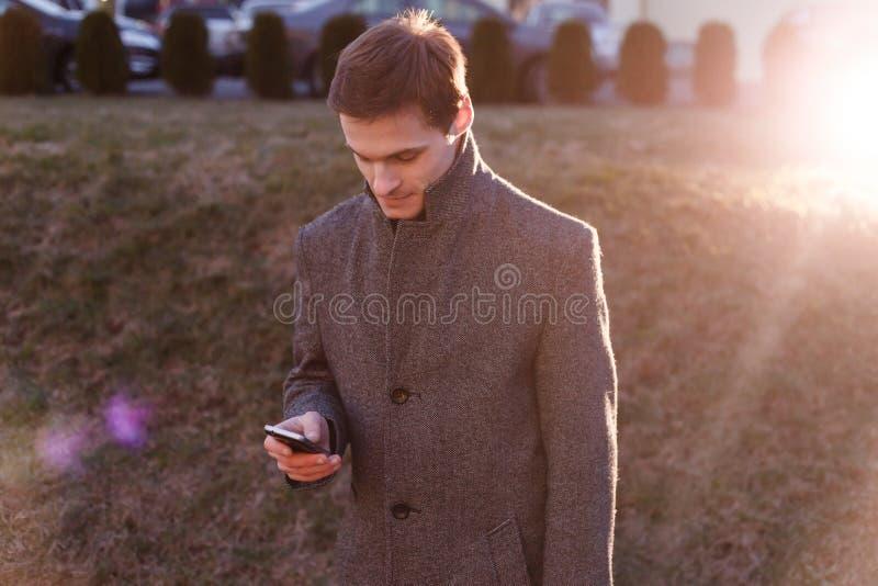 Een knappe jonge zakenman gebruikend zijn telefoon en zich bevindt op de straat in de avond stock afbeeldingen