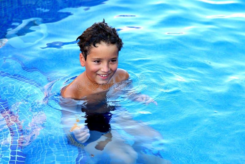 Een knappe jongen speelt in een zwembad royalty-vrije stock afbeelding