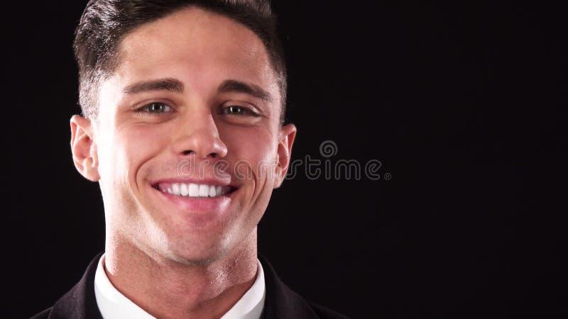 Een knappe kerel kijkt peinzend en glimlacht dan in de camera stock afbeelding