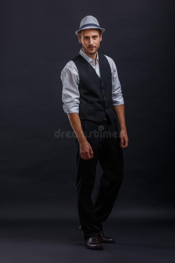 Een knappe kerel in een retro kostuum met een vest en het dragen van een hoed die terwijl status stellen royalty-vrije stock foto's