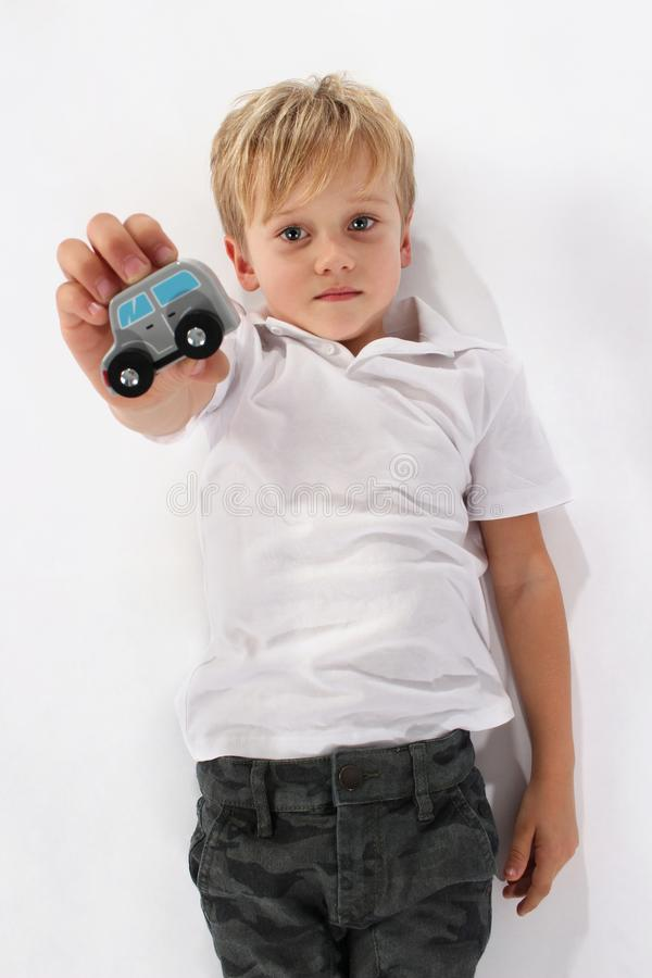 Een knappe kleine kindjongen die op de vloer op zijn rug liggen die een houten autostuk speelgoed steunen royalty-vrije stock fotografie