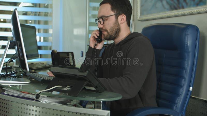 Een knappe mannelijke arbeider in een call centrebureau die op een telefoon spreken stock foto's