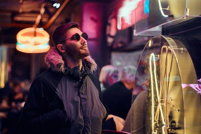 Een knappe mens die een laag en zonnebril dragen met dient zakken in, die zich in de nacht op de straat bevinden royalty-vrije stock fotografie