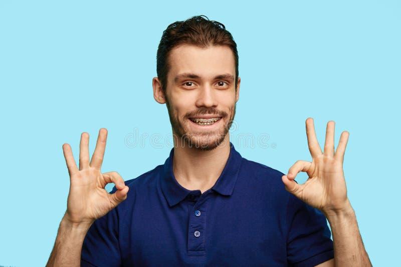 Een knappe mens die o.k. teken tonen dat op blauwe achtergrond wordt geïsoleerd royalty-vrije stock foto's