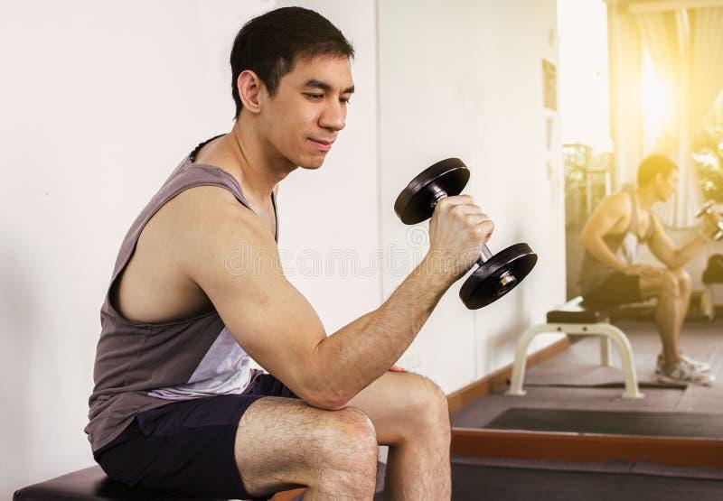 Een knappe mens is oefening in de gymnastiek stock fotografie