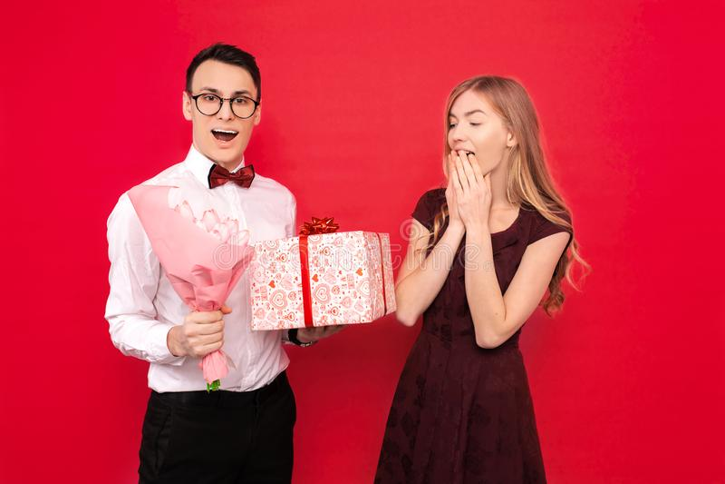 Een knappe student, die glazen dragen, geeft een gift en een boeket van bloemen aan zijn meisje tegen een rode achtergrond stock afbeelding