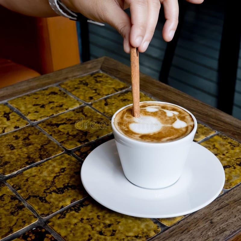 Een koffiekop Latte die door pijpjes kaneel worden bewogen royalty-vrije stock fotografie