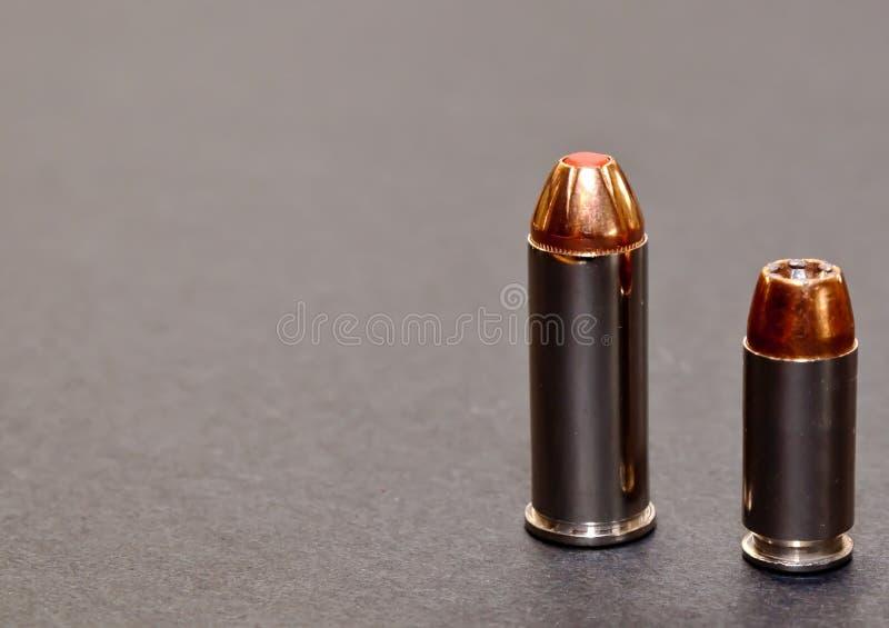 Een kogel van het 40 kaliber holle punt en een rode getipte kogel van 44spl samen op een grijze achtergrond royalty-vrije stock afbeeldingen