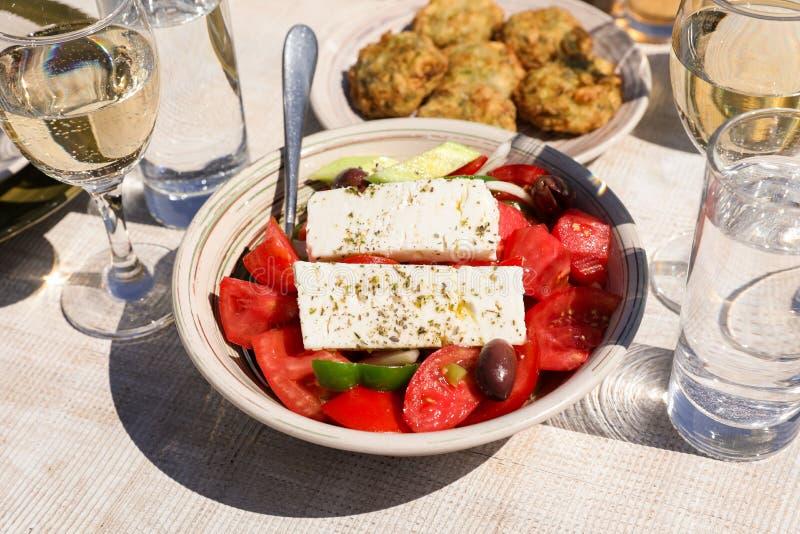 Een kom dorps Griekse salade naast courgetteballen plateert en witte die wijn, waterglazen in Griekse herberg worden gediend royalty-vrije stock fotografie