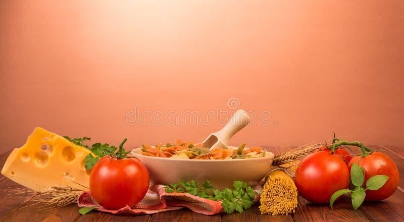 Een kom farfalle en houten lepel, bos van spaghetti, tomatoe royalty-vrije stock foto