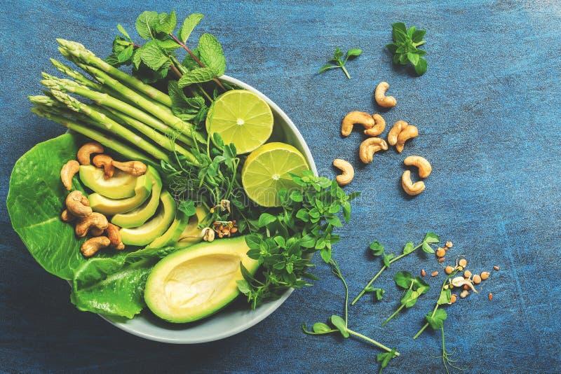 Een kom groene veganistsalade met asperge, avocado, sla, basilicum, munt, microgreen, kalk en cashewnoten, blauwe plattelander stock afbeeldingen