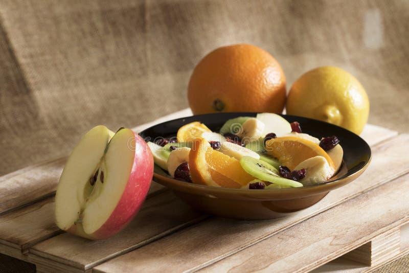Een kom van fruitsalade, een sinaasappel, een citroen en een halve appel stock foto's