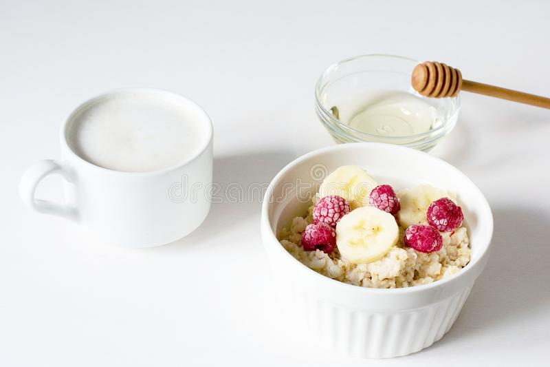 Een kom van havermeel op een witte achtergrond Gezond Ontbijt stock foto's