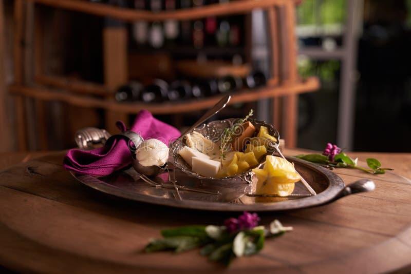 Een kom van mascarponekaas in een lepel voor roomijs op een oud dienblad, naast een schotel met schimmelkaas, Bruno st, carambola stock afbeelding