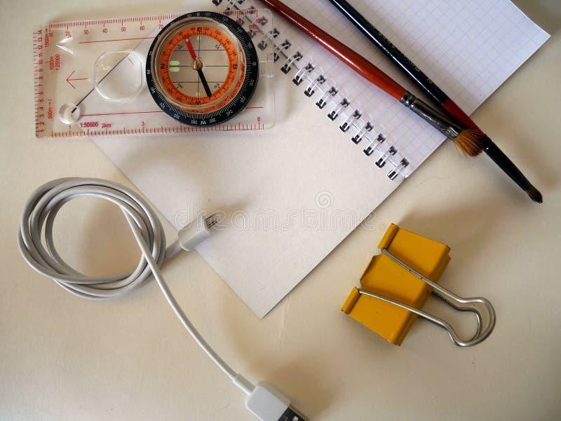 Een kompas en voorwerpen op een witte achtergrond stock afbeeldingen