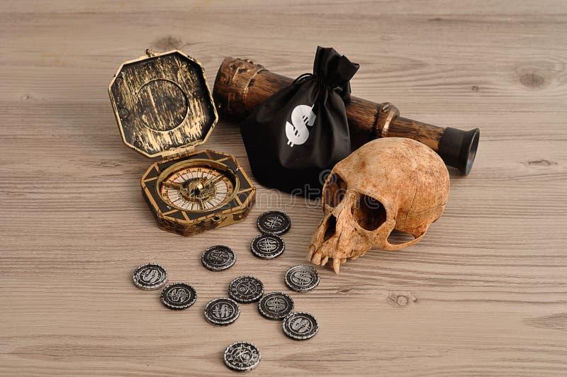Een kompas, het oogglas en de muntstukken en een geld doen voor een piraatspel in zakken met een aapschedel royalty-vrije stock foto's