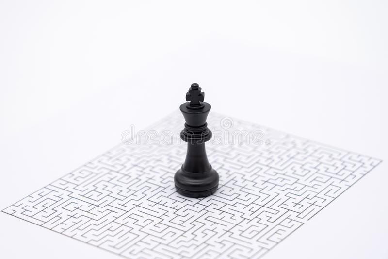Een Koning Chess wordt geplaatst op het centrum van het labyrint Het Oplossen van problemenanalyse van bedrijfsideeconcepten van  royalty-vrije stock afbeeldingen