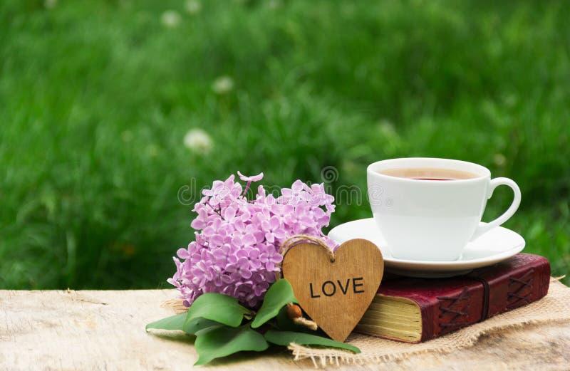 Een kop hete thee, een boek en seringen tegen een achtergrond van groen gras Romantisch concept Houten kaart met een hart royalty-vrije stock afbeeldingen