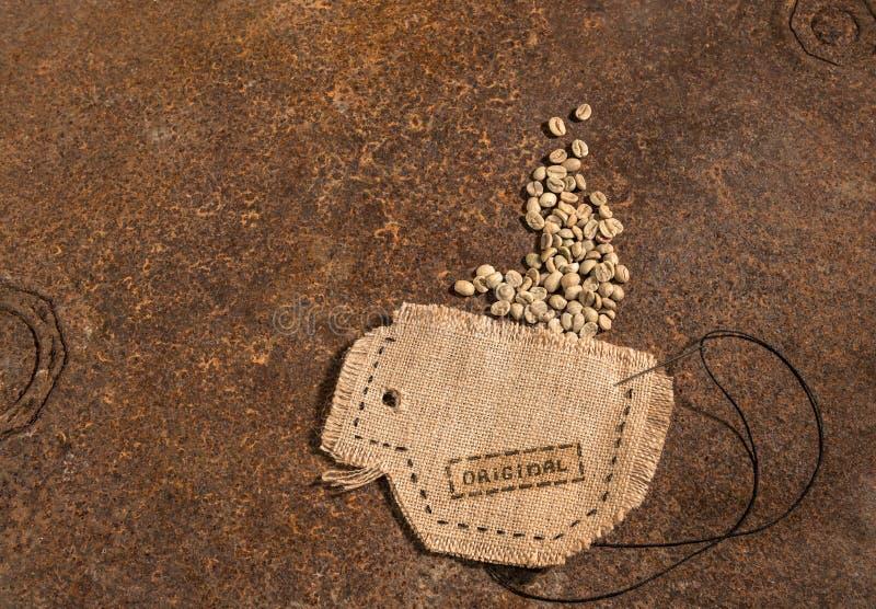 Een kop in jutehoogtepunt wordt genaaid van koffiebonen die stock foto's