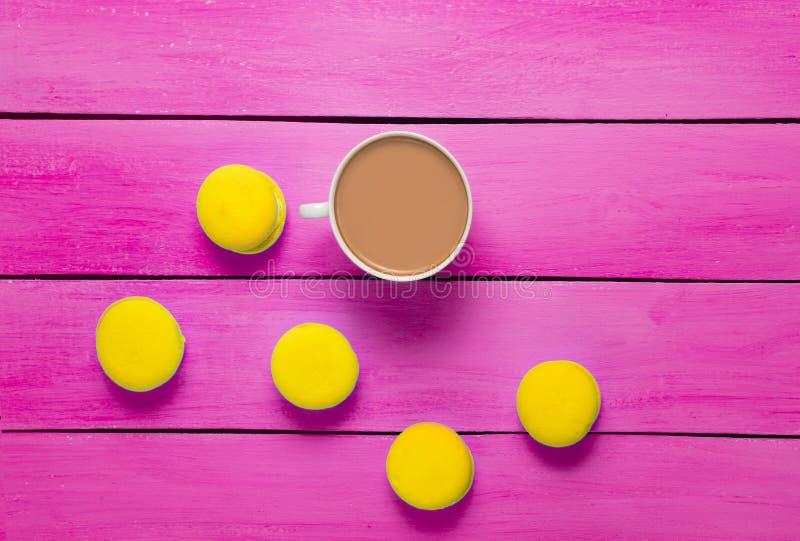 Een kop koffie en gele makarons op roze houten lijst Tre royalty-vrije stock afbeelding
