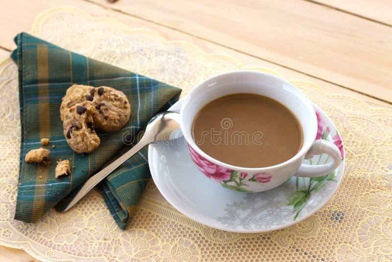 Een kop koffie en koekjes op het hout stock fotografie
